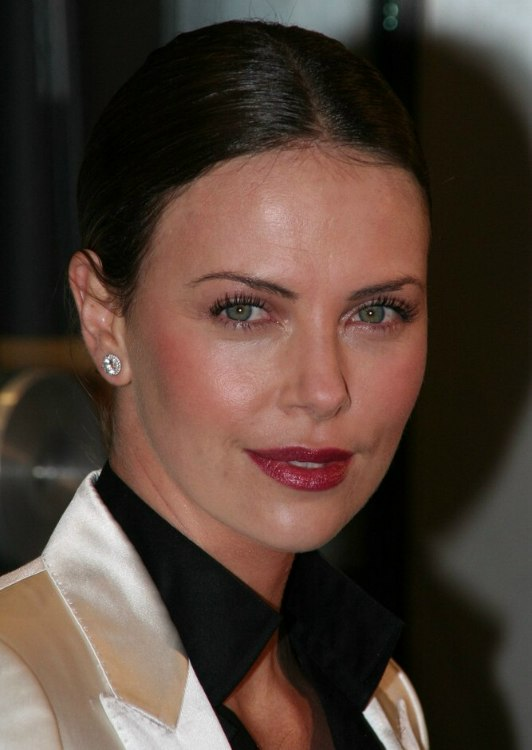 Charlize Theron  Hair in a severely brushed back style and a large chignon