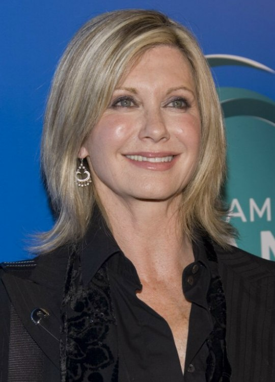 Olivia Newton John wearing her hair in a medium hairstyle suitable for fine or thin hair