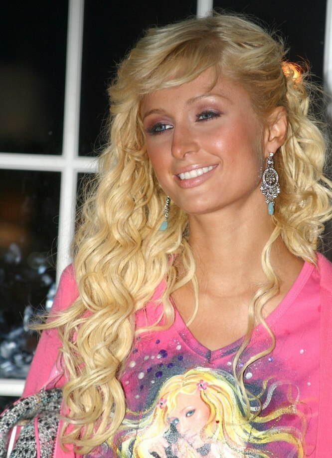 Paris Hilton with her long wavy hair styled behind one ear