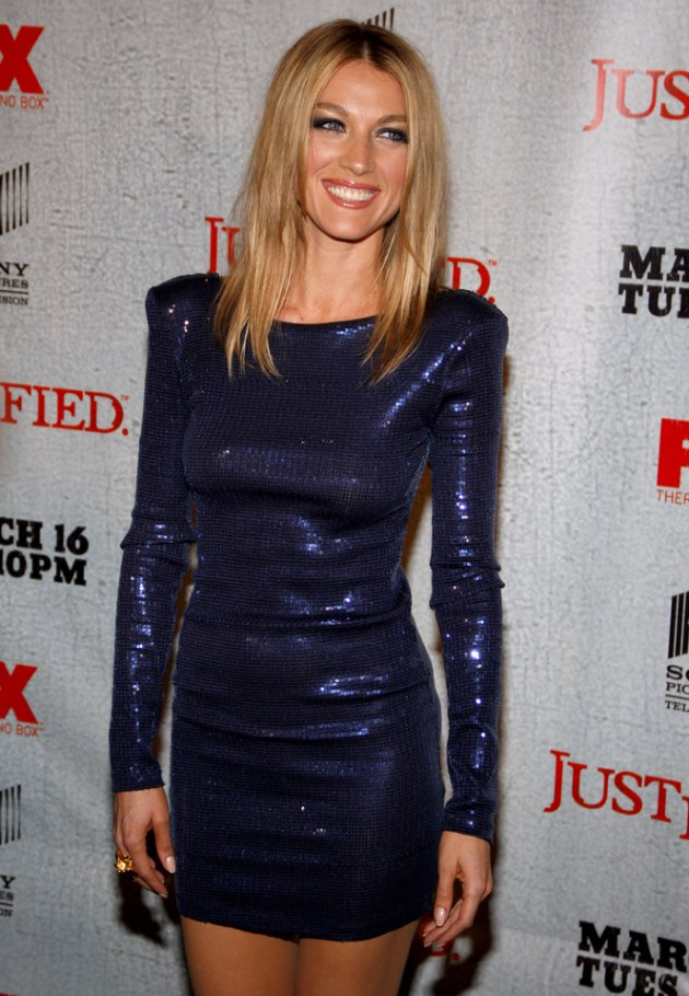 Natalie Zea with her long hair parted in the middle and angled along the sides