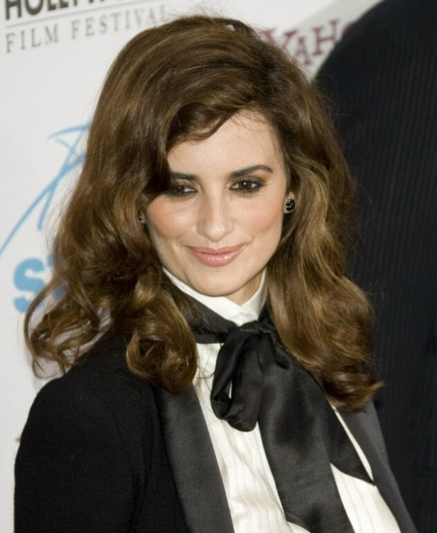 Penlope Cruz with long curly hair and wearing a tux outfit