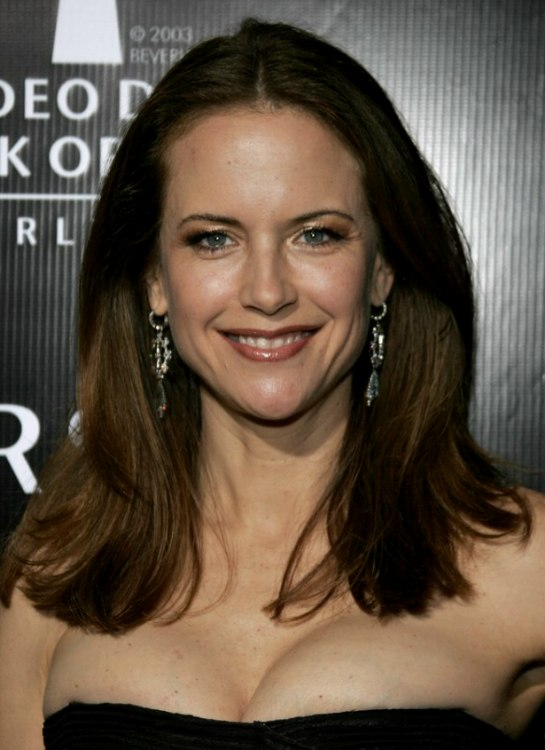 Kelly Preston wearing her long brunette hair cut bluntly and parted in the middle