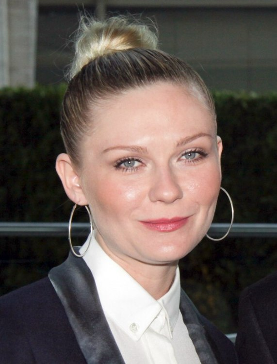 Kirsten Dunst With Her Hair In A Tight Bun And Wearing A