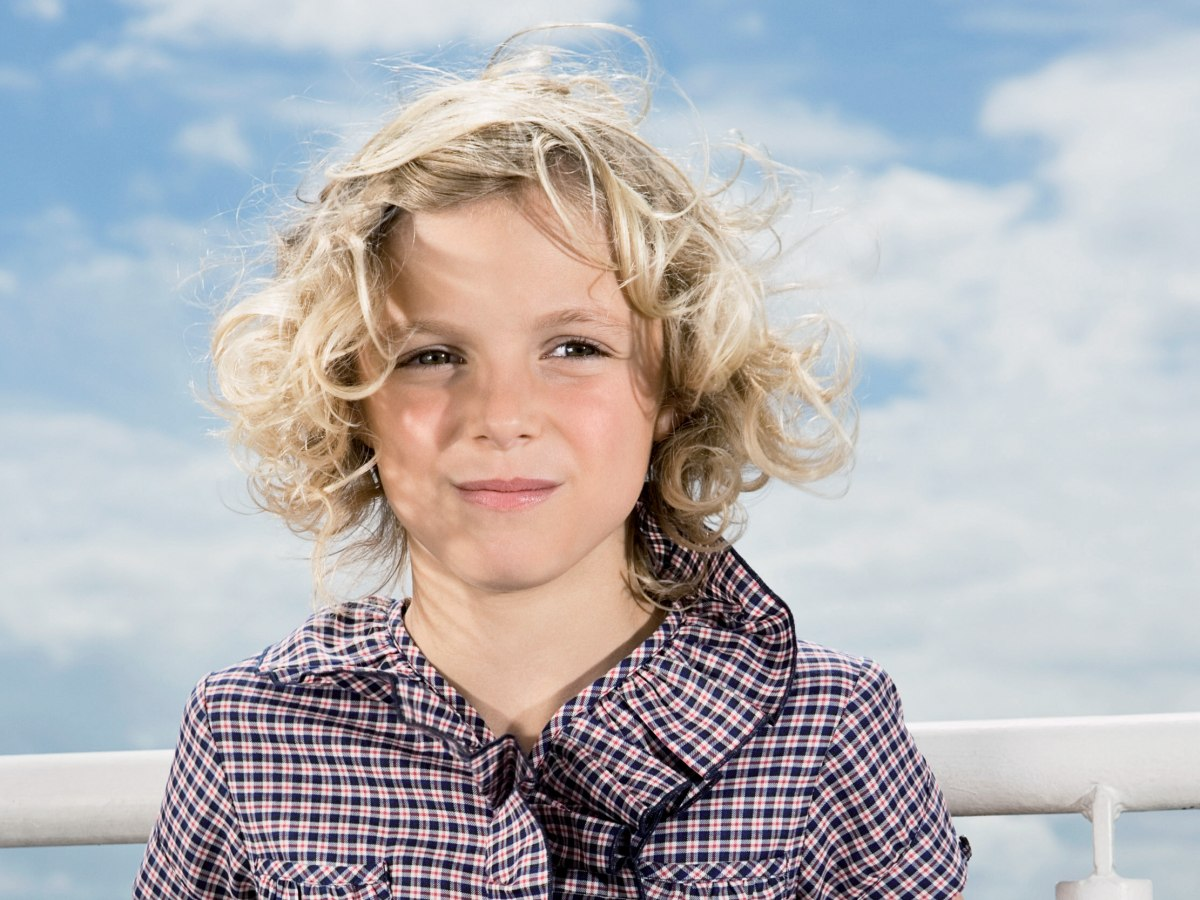 Girl With Blonde Curls In A Hairstyle With Chin Long Sides