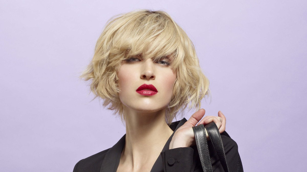 Blonde chin length bob with undone styling and thick bangs with movement to the side