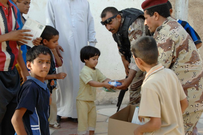 An Iraqi soldier gives a little girl a Halal meal in Amarah, Iraq on July 4, 2008. The meals were handed out to build a relationship with the people of Amarah. (U.S. Army photo by Spc. Lester Colley/Released)