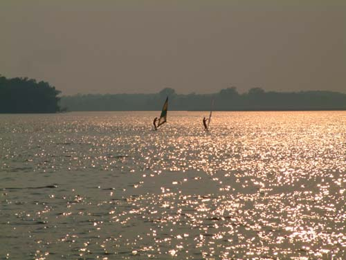Two windsurfers on a shimmering lake at dusk