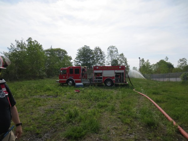 A firetruck pumps water to a burning building