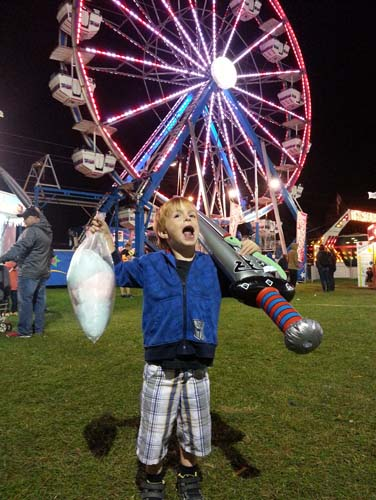 An image of a young boy celebrating his wins at the fair grounds midway