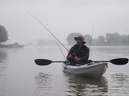 A fisherman casting reeling in a large fish in the Grand River