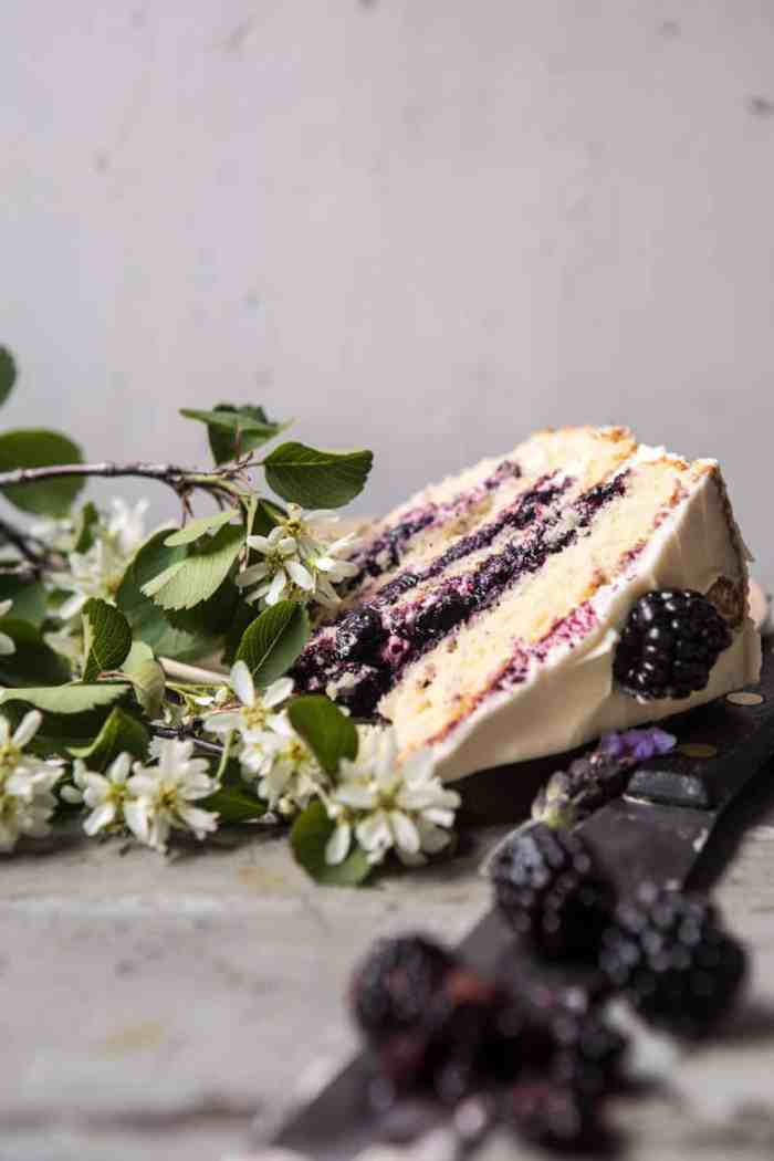 side angled photo of Blackberry Lavender Naked Cake with White Chocolate Buttercream with one slice
