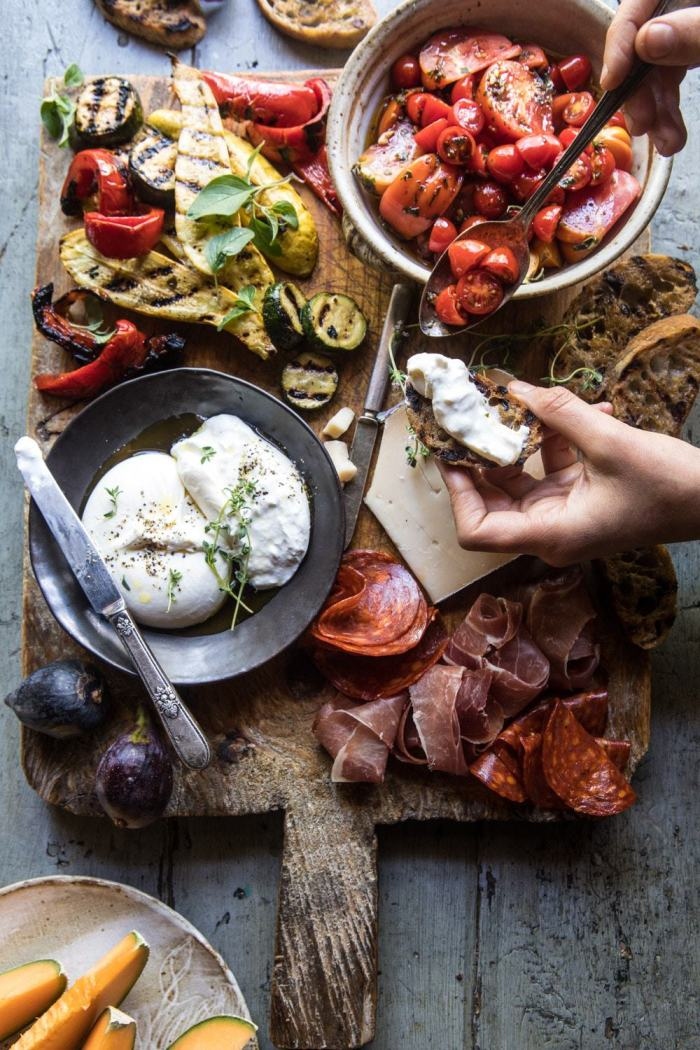 overhead photo of Marinated Tomato and Grilled Veggie Cheese Board with hands in photo