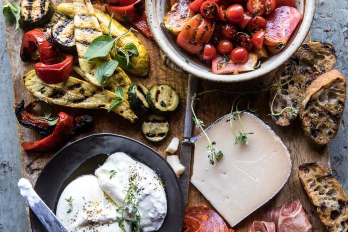 horizontal overhead photo of Marinated Tomato and Grilled Veggie Cheese Board