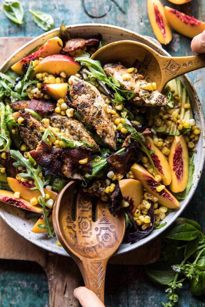tossing the Rosemary Chicken, Caramelized Corn, and Peach Salad with salad spoons
