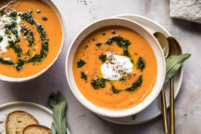 horizontal photo of Golden Sweet Potato Soup with Burrata and Sage Pesto with bread on table