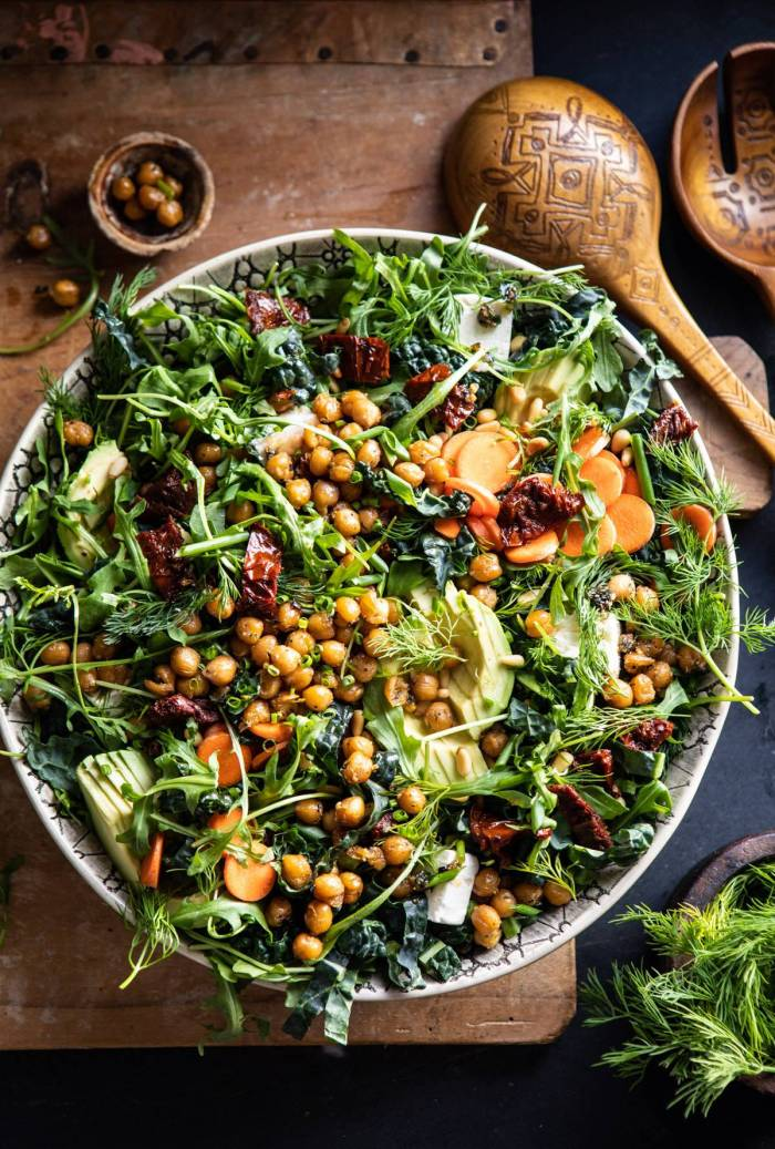 overhead photo of Super Green Sun-Dried Tomato Herb Salad with Crispy Chickpeas with salad spoons and fresh herbs in photo