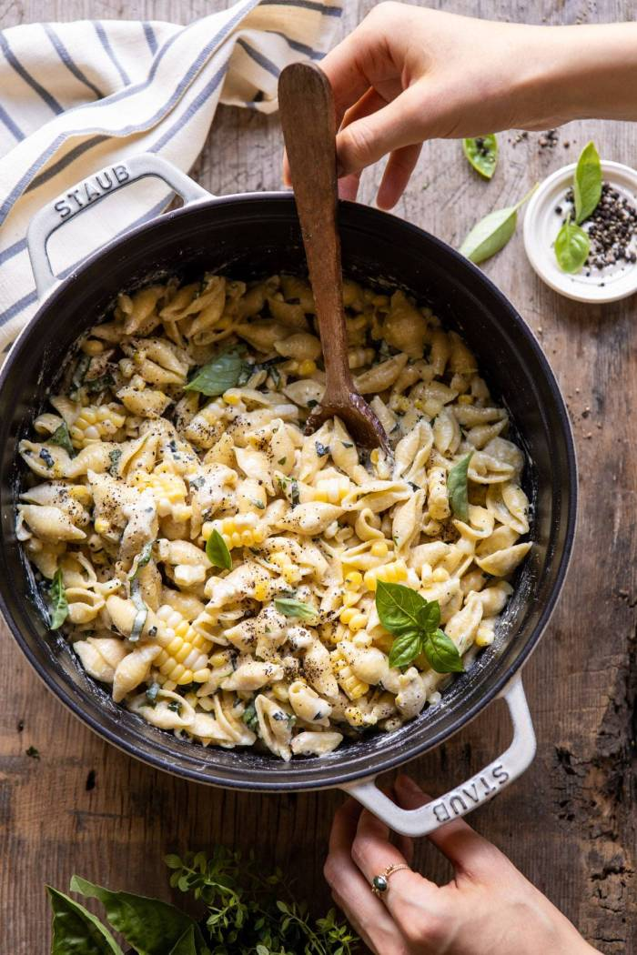 overhead photo of One Pot Lemon Basil, Corn, and Ricotta Pasta with hands on pot and wooden spoon in pot
