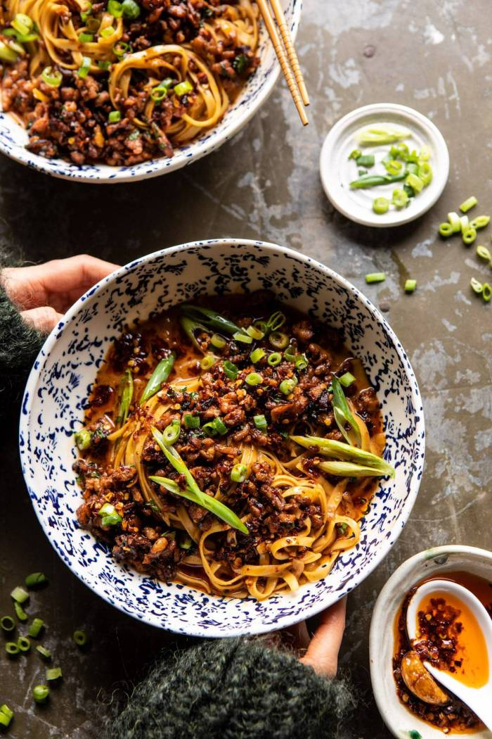 overhead photo of Better Than Takeout Dan Dan Noodles with hands on bowl