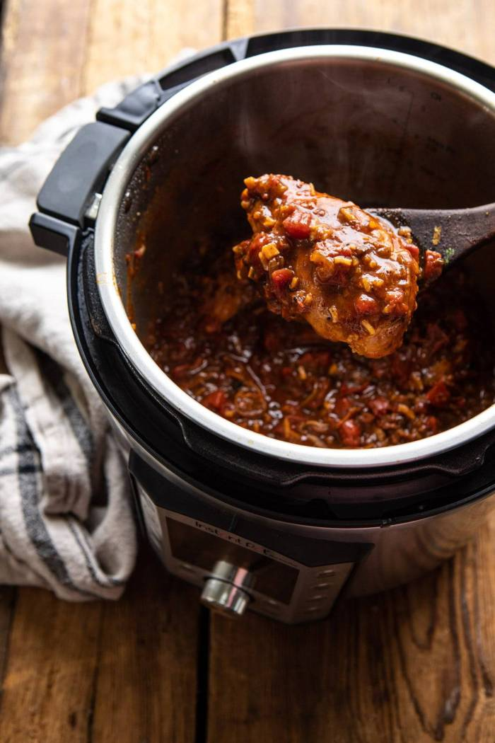 Healthier 30 Minute Beer Braised Chicken in instant pot with spoon picking chicken up out of instant pot