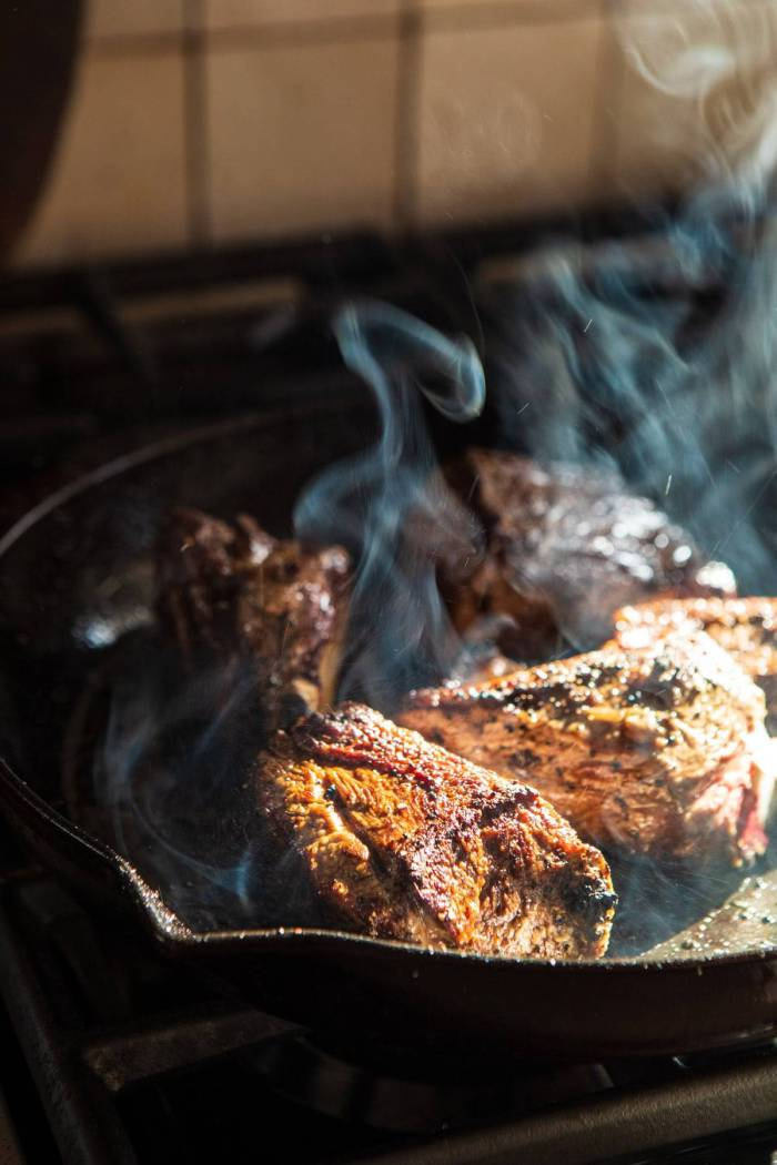 short ribs being seared on the stove in skillet