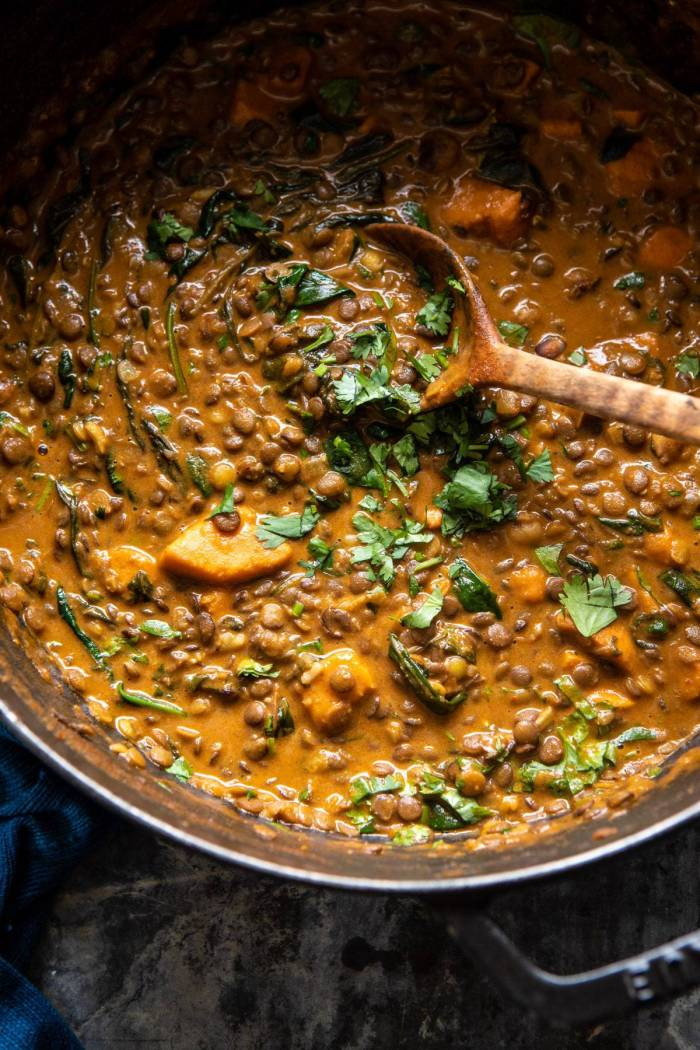 overhead photo of Sweet Potato Lentil Curry in pot with wooden spoon in curry