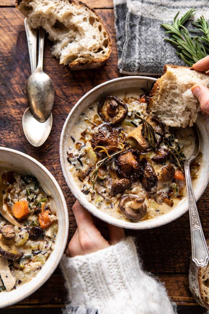 overhead photo of Creamy Wild Rice Chicken Soup with Roasted Mushrooms in soup bowls with hands on bowl and bread in soup