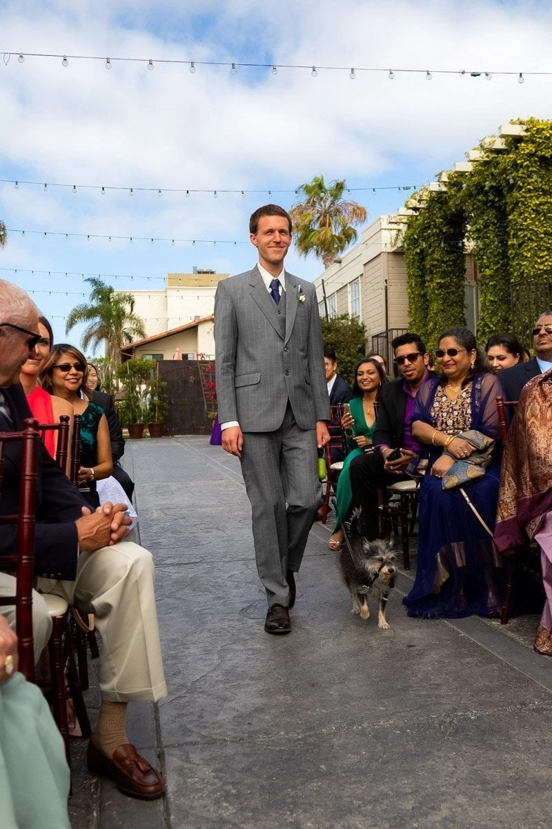 groom and his dog walking down the aisle