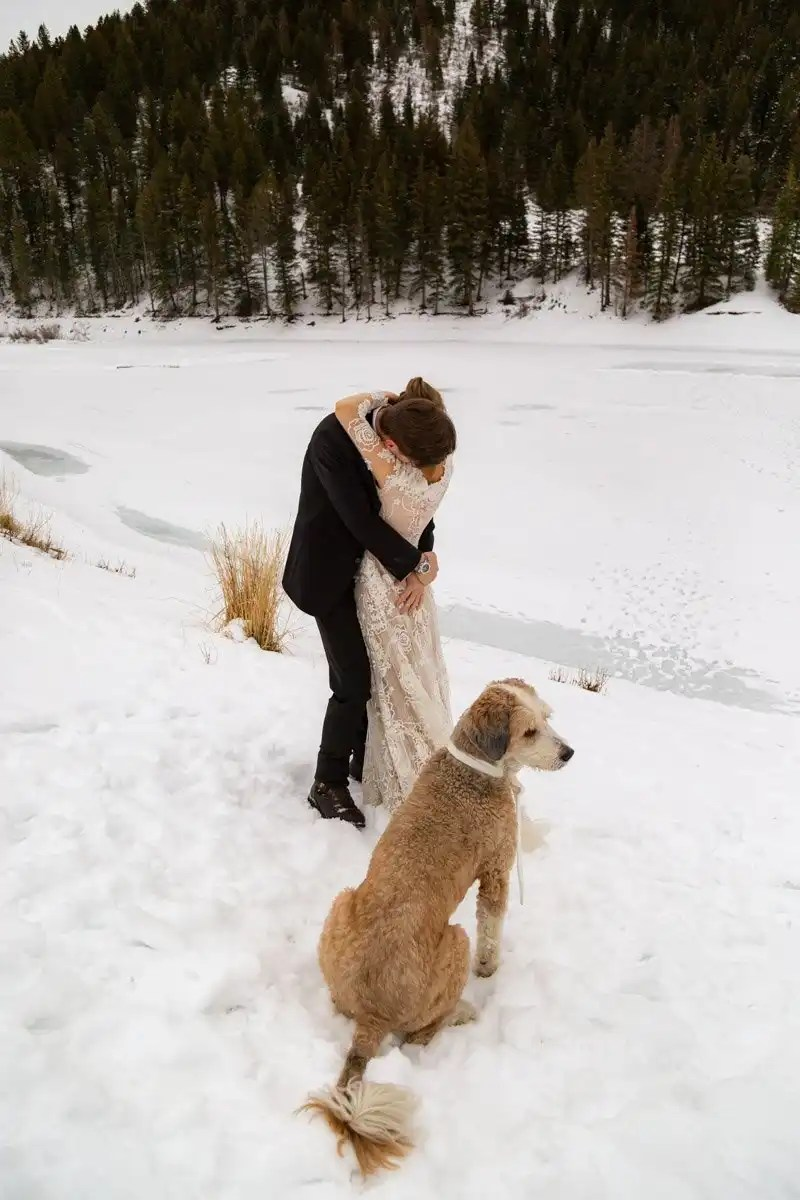 newlyweds with their pup in the snow