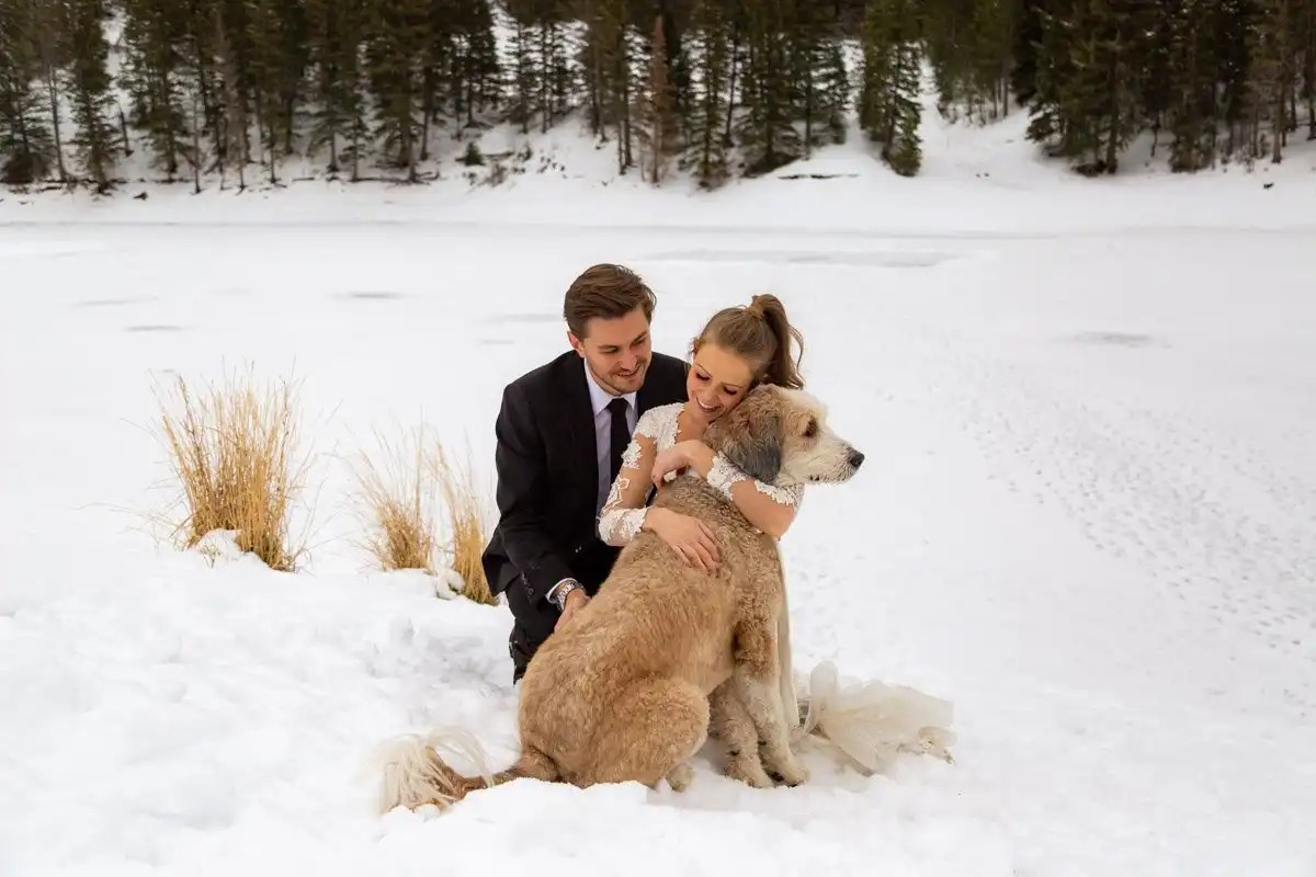 a love filled couple cuddles their dog during their winter mountain elopement
