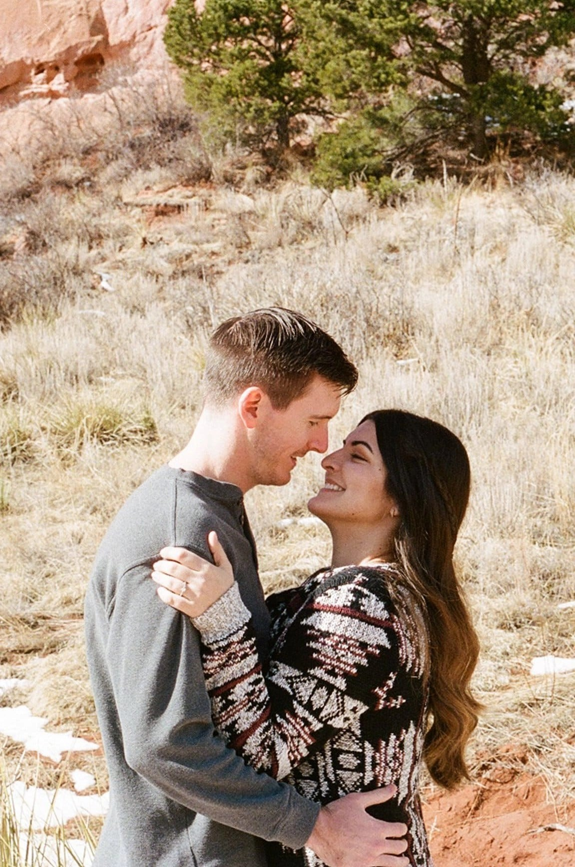 Couple kissing on film during their engagement session in Garden of the Gods