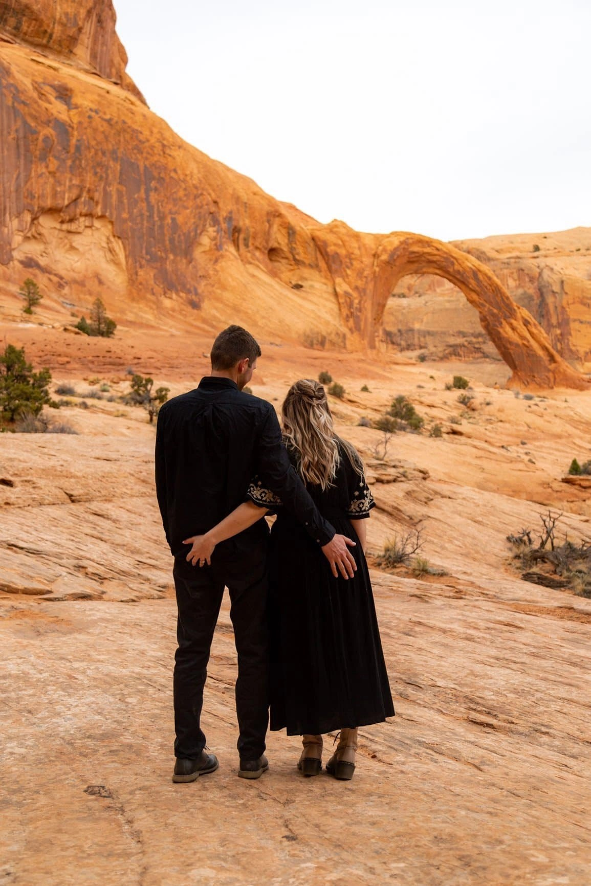 Intimate couple in front of the Corona Arch in Moab. Go out and adventure safely with those you love