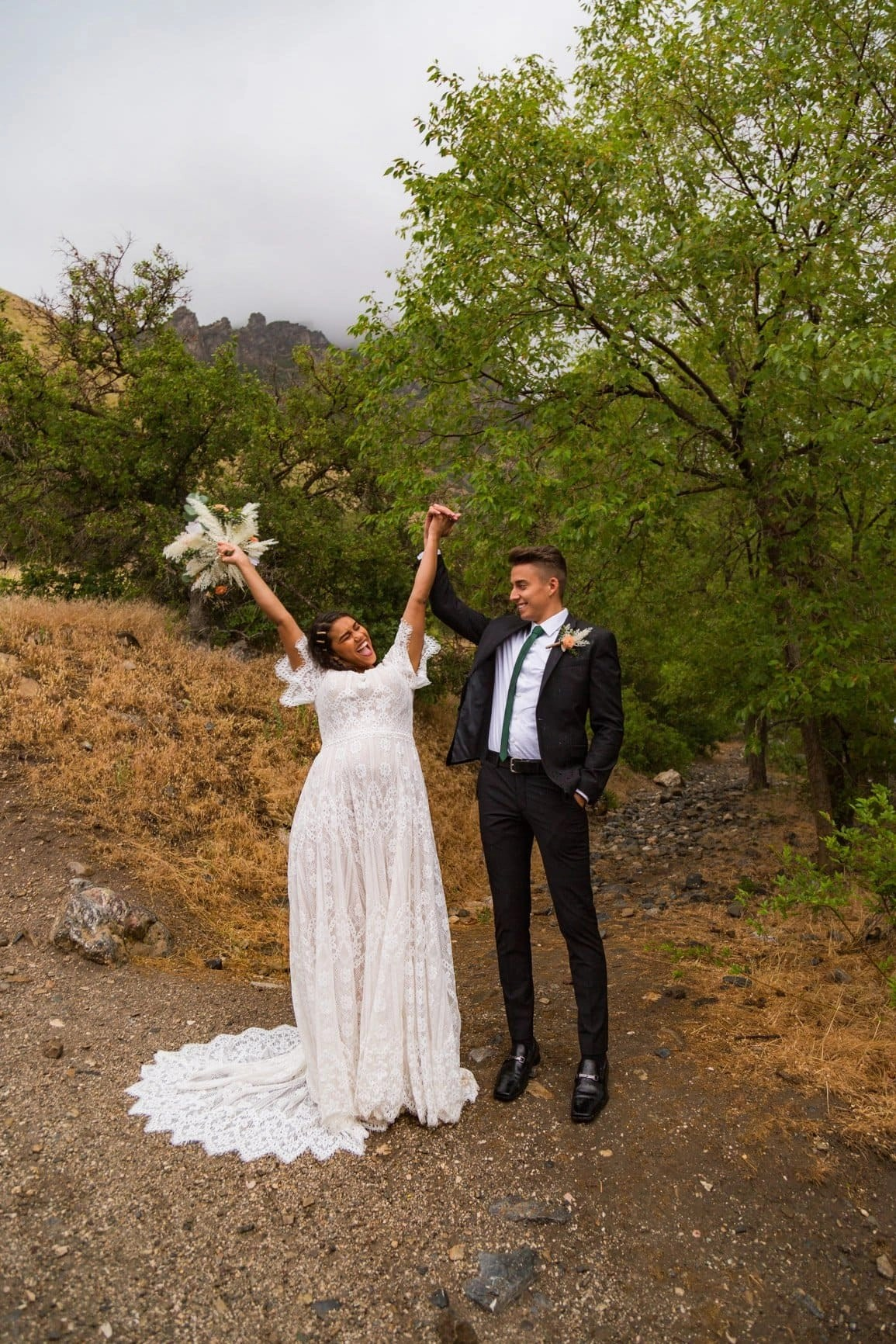 husband and wife celebrate their love by raising their hands in a forest in utah
