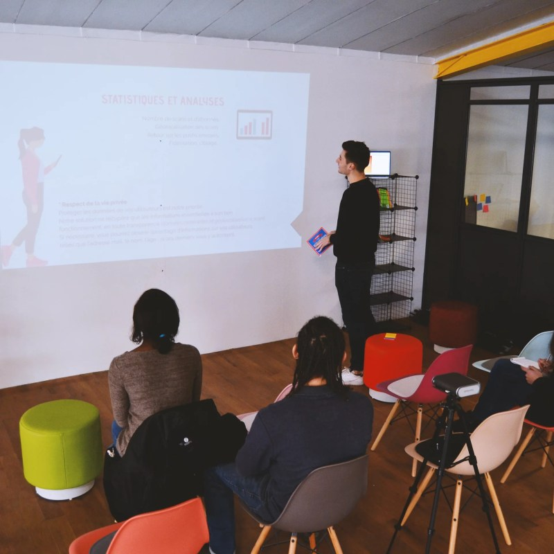 deux personnes écoutant une présentation lors d'une formation pour représenter l'offre salle de réunion et formation du hall 24 à Rouen