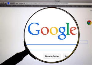 Google home page with magnifying glass over the search bar and logo