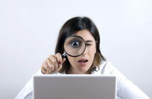 Woman with magnifying glass looking at laptop screen