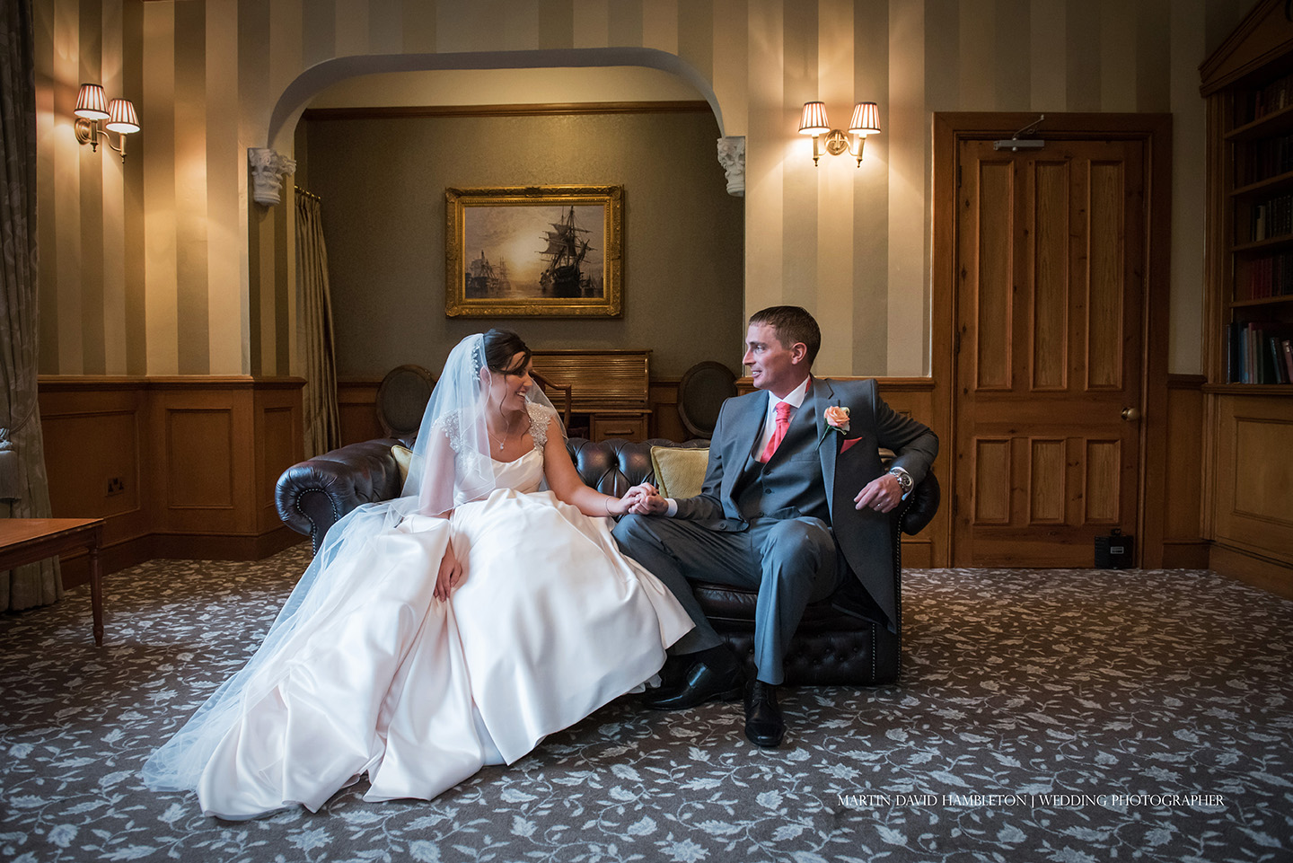 bride and groom portrait in the library at Nunsmere Hall