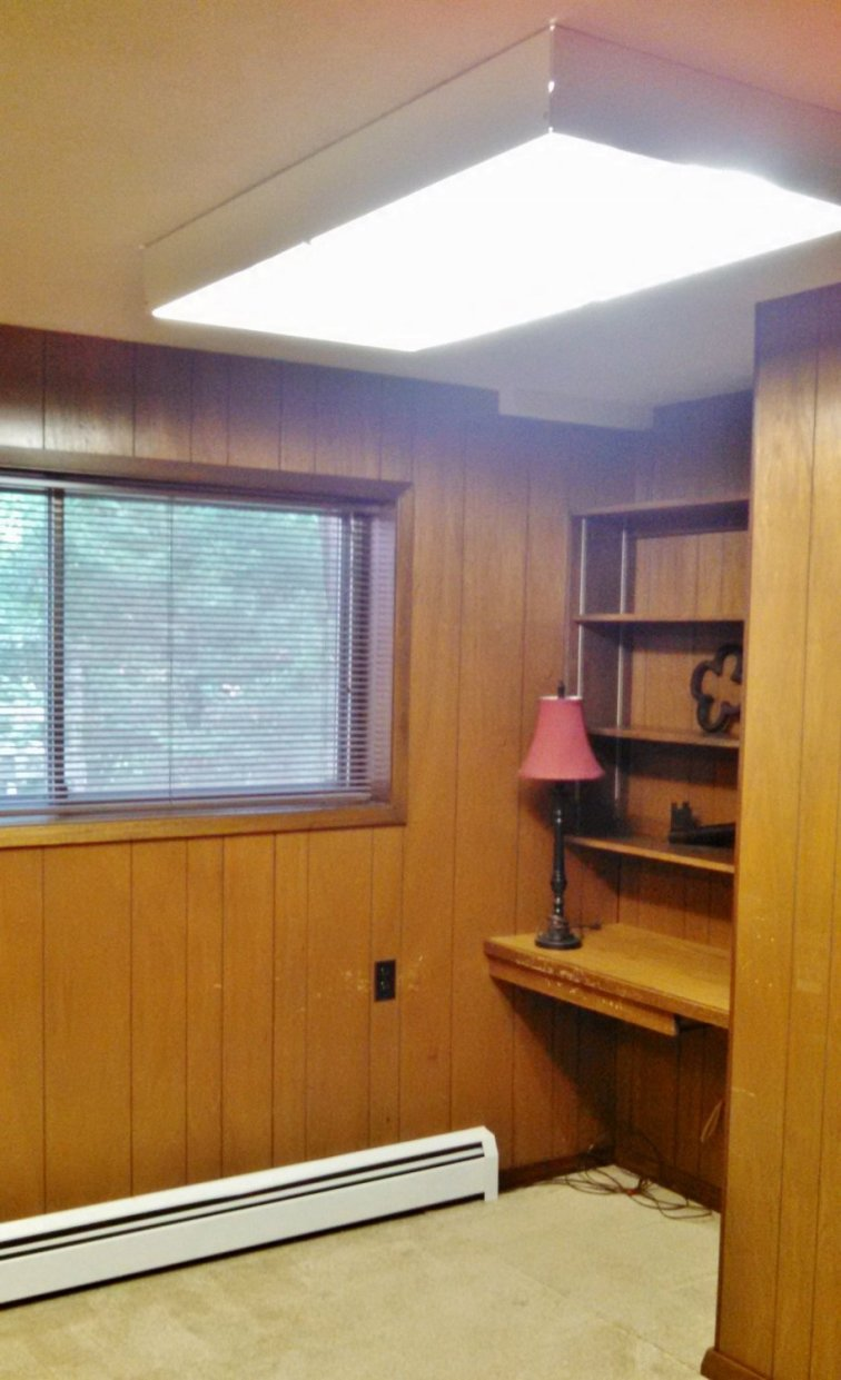Dark wood-panel room before updating to a bright craft room