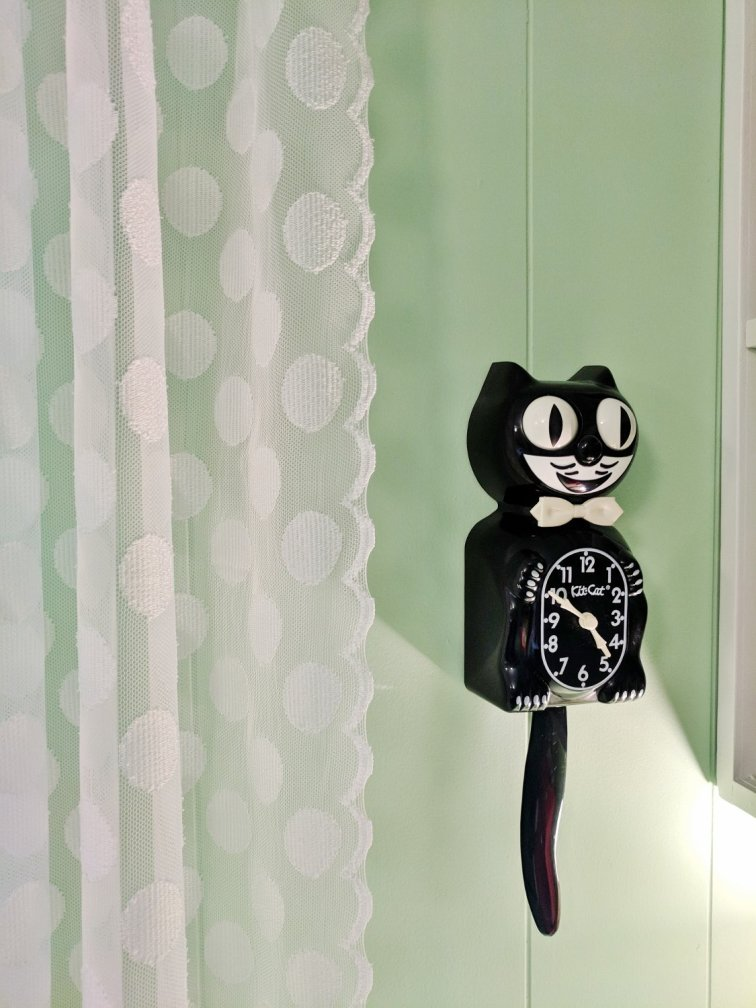 Retro craft room makeover with mint green walls and a Kit-Cat clock