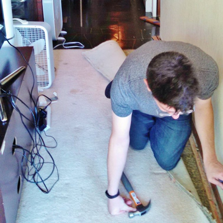 Removing baseboards and carpet to prepare for hardwood installation