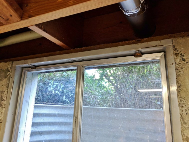 Figuring out how to hang curtains in a tricky basement window with an uneven wall