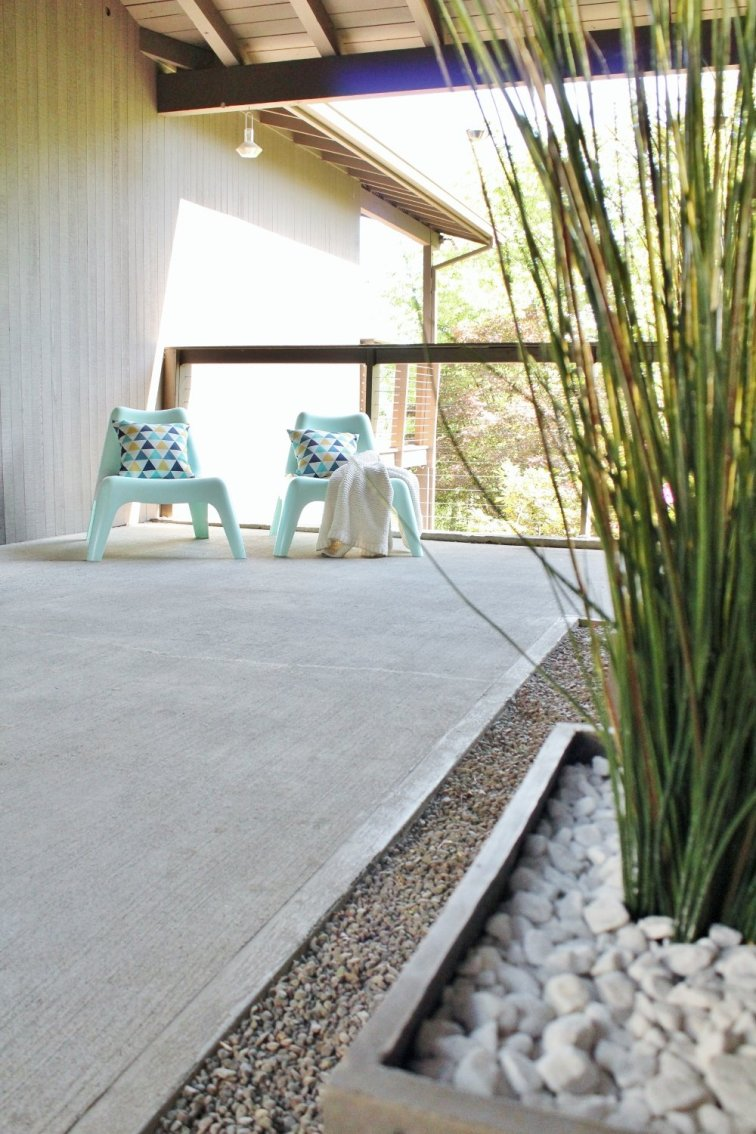 Mid-century modern breezeway with turquoise lounge chairs and modern planters