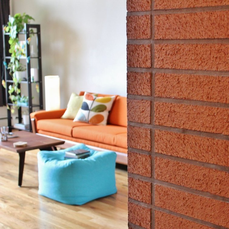 Brick chimney in mid-century modern living room with orange couch in the background
