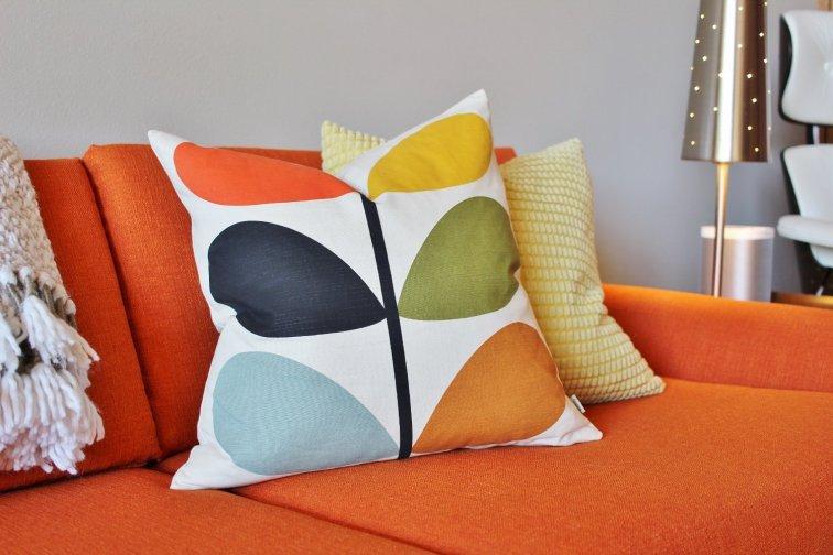 Mod Orla Kiely stem throw pillow on an orange sofa