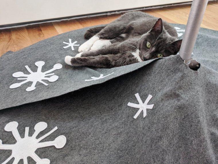 Cat snuggled up on mid-century modern Christmas tree skirt
