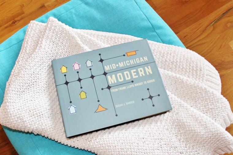 Mid-Michigan Modern coffee table book on an ottoman