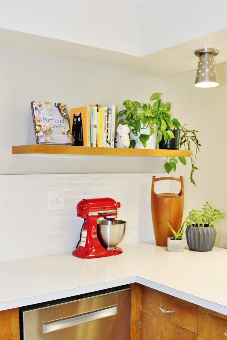 Modern floating shelf holding cookbooks and plants