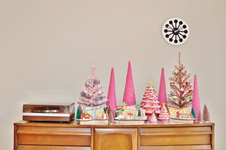 Pink Christmas tree village displayed on vintage sideboard