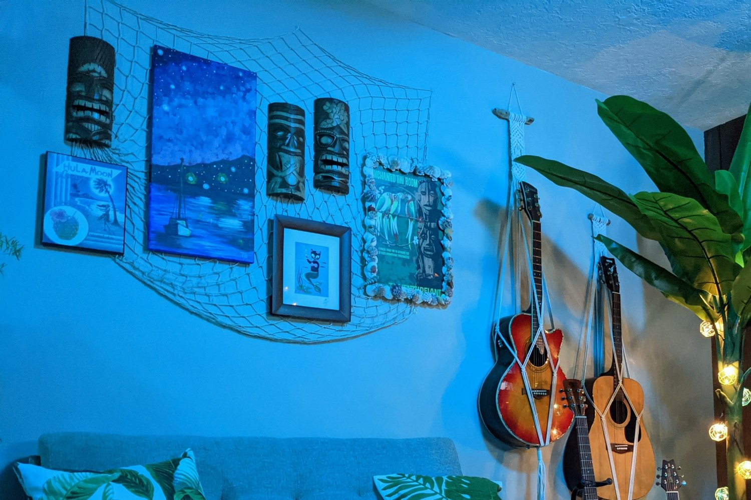 Tiki bar gallery wall at night with romantic blue lighting and nautical string lights