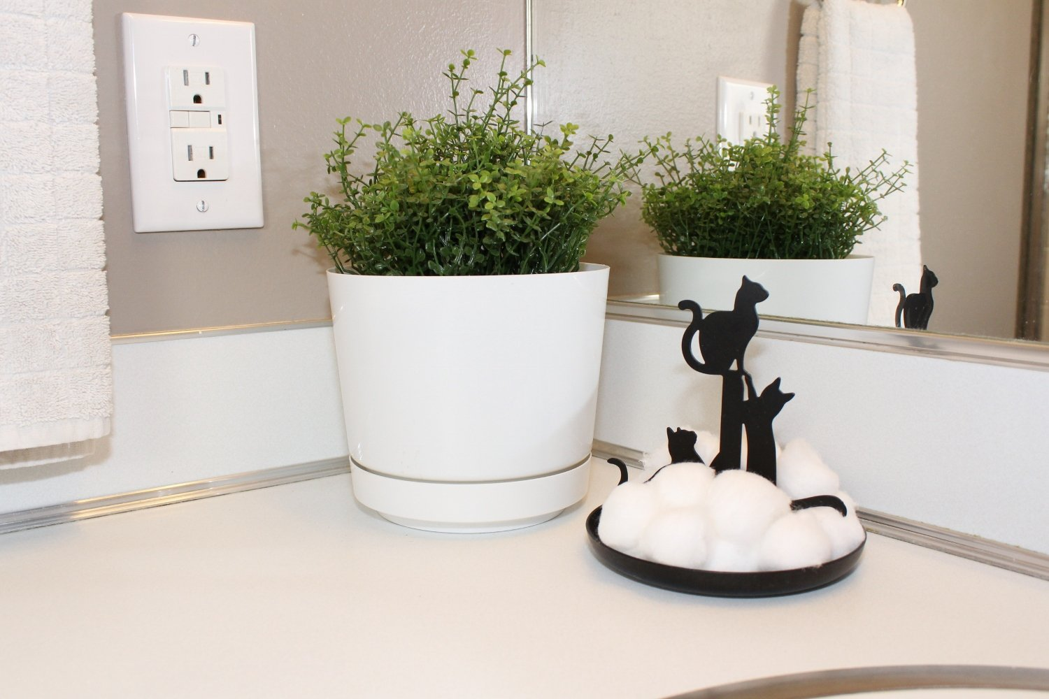 White countertop in mid-century modern bathroom with cat cotton ball holder and houseplant
