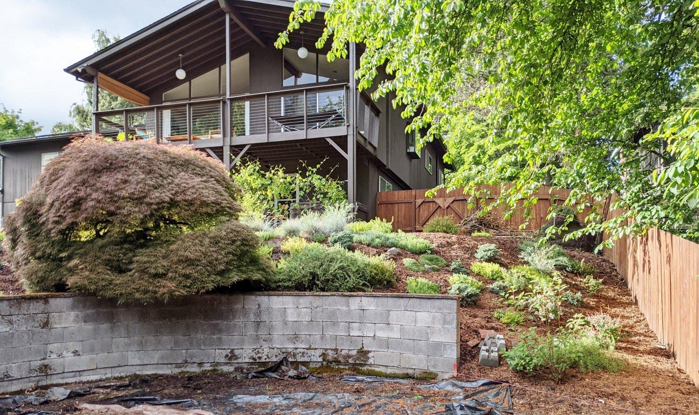 Original cinder block retaining wall in mid-century modern backyard